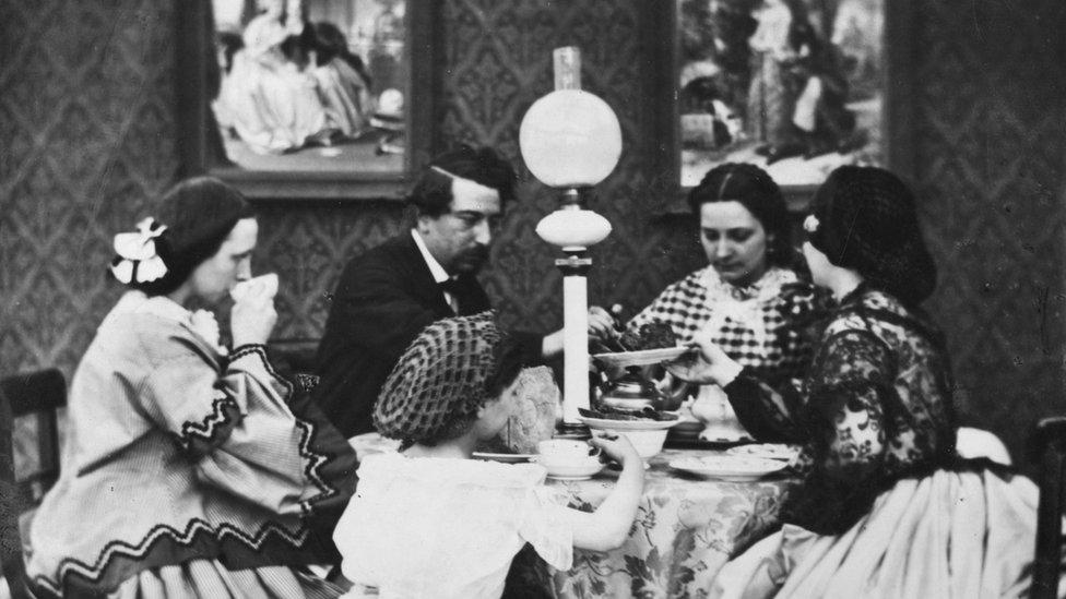 Una familia ante una mesa con luz eléctrica en una vivienda en el siglo XIX.