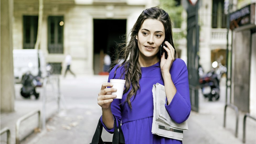 Mujer caminando y hablando por el celular