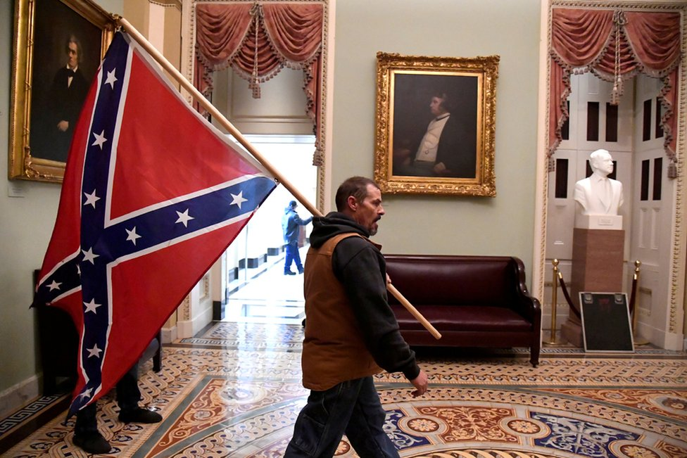 A supporter of President Donald Trump carries a Confederate flag on the second floor of the US Capitol near the entrance to the Senate after breaching security defences, in Washington DC. 6 January 2021.
