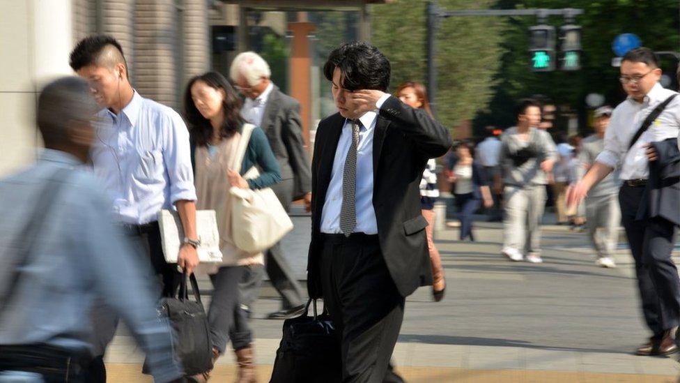 Un hombre de negocios japonés camina con sueño por Tokyo.