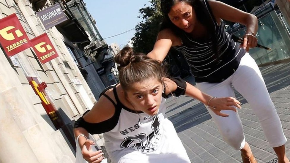 امرأة وفتاة تحاولان الفرار من موقع الهجوم في لاس رامبلاس