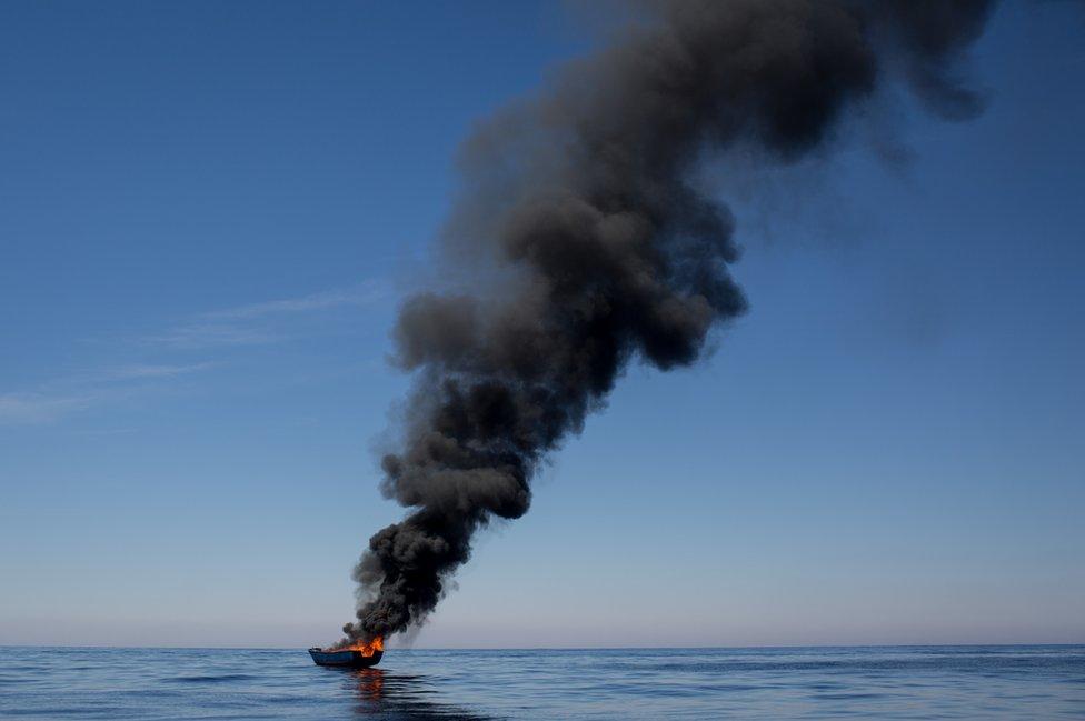 Un pequeño bote se quema después que hubiera sido abandonado por un grupo de refugiados y migrantes cerca de la costa italiana.