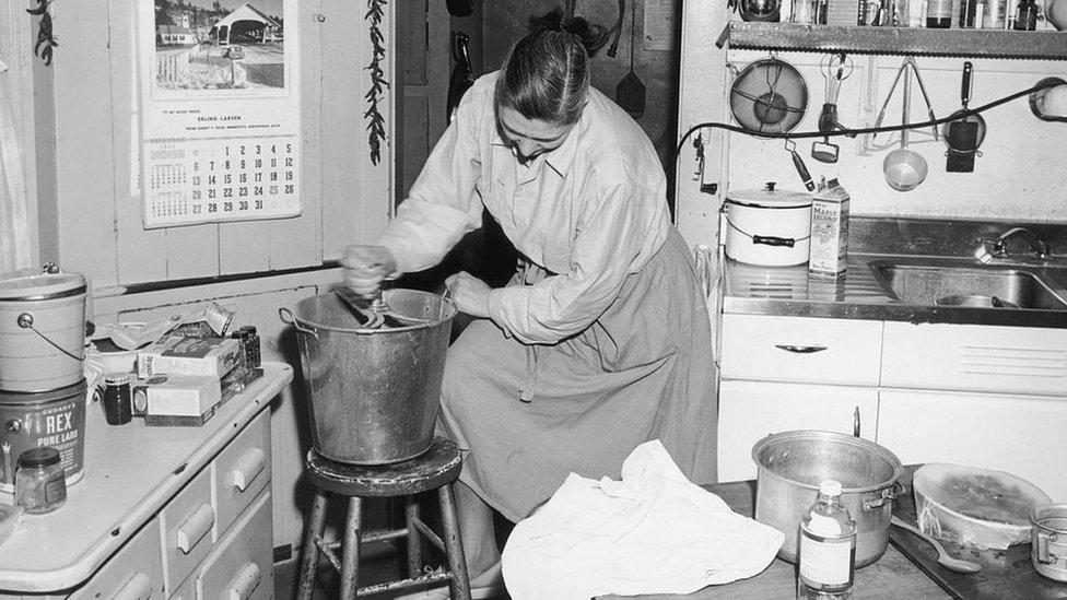 Mujer vigorosamente mezclando la masa del pan.