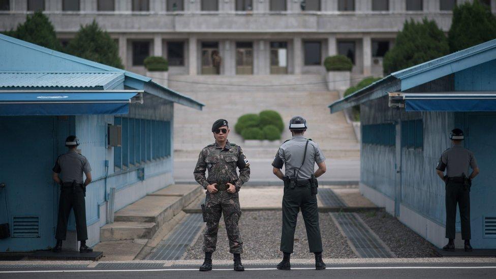 Dalam sebuah foto yang diambil pada tanggal 2 Agustus 2017, tentara Korea Selatan berjaga-jaga di depan Panmon Hall (sisi C) Korea Utara dan garis demarkasi militer yang memisahkan Korea Utara dan Selatan, di Panmunjom, di Area Keamanan Bersama Zona Demiliterisasi.