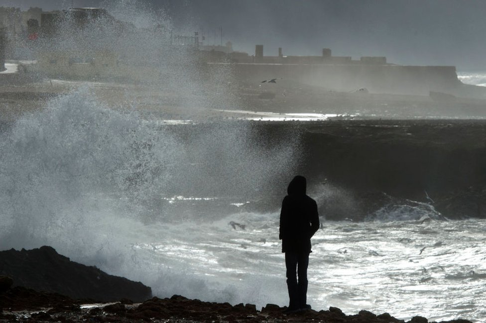 مغربي يمشي منفردا، الاثنين، قرب شاطئ العاصمة الرباط إثر عاصفة صاحبها طقس بارد في مختلف أنحاء المغرب خلال الأيام القليلة الماضية.
