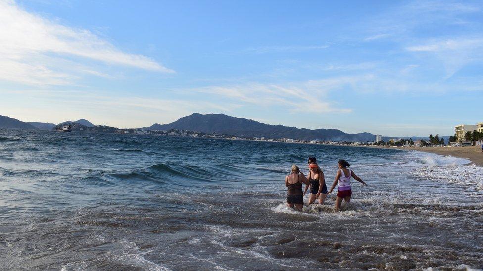 Turistas jugando en las olas.