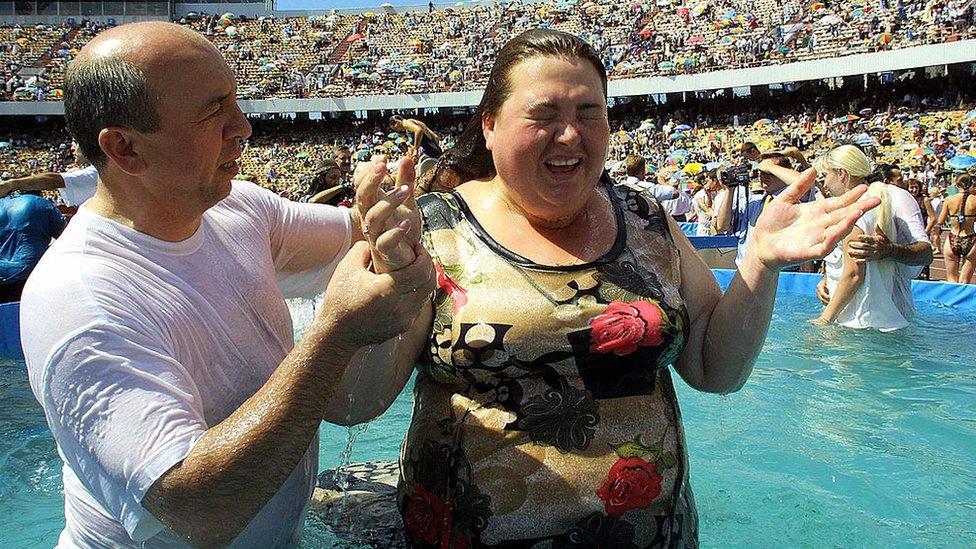 Una mujer participa de un bautizo masivo.
