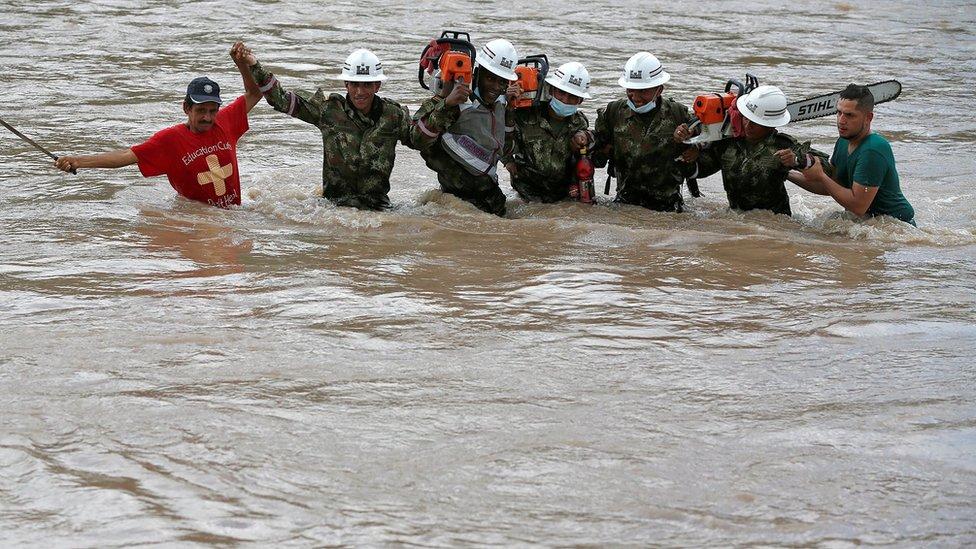 Hombres tratan de cruzar un río crecido en Putumayo