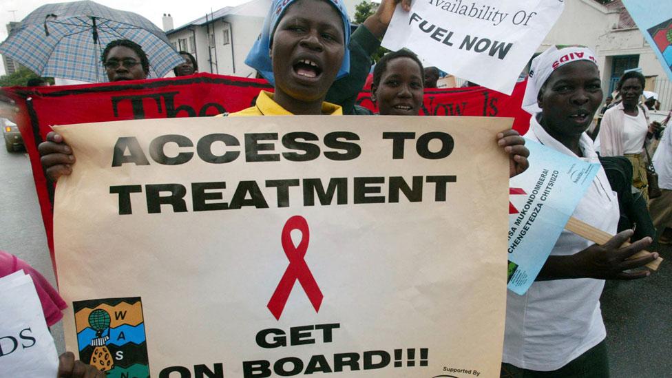 Mujeres en Zimbabue con carteles que exigen acceso a medicamentos antiretrovirales para trata el VIH.