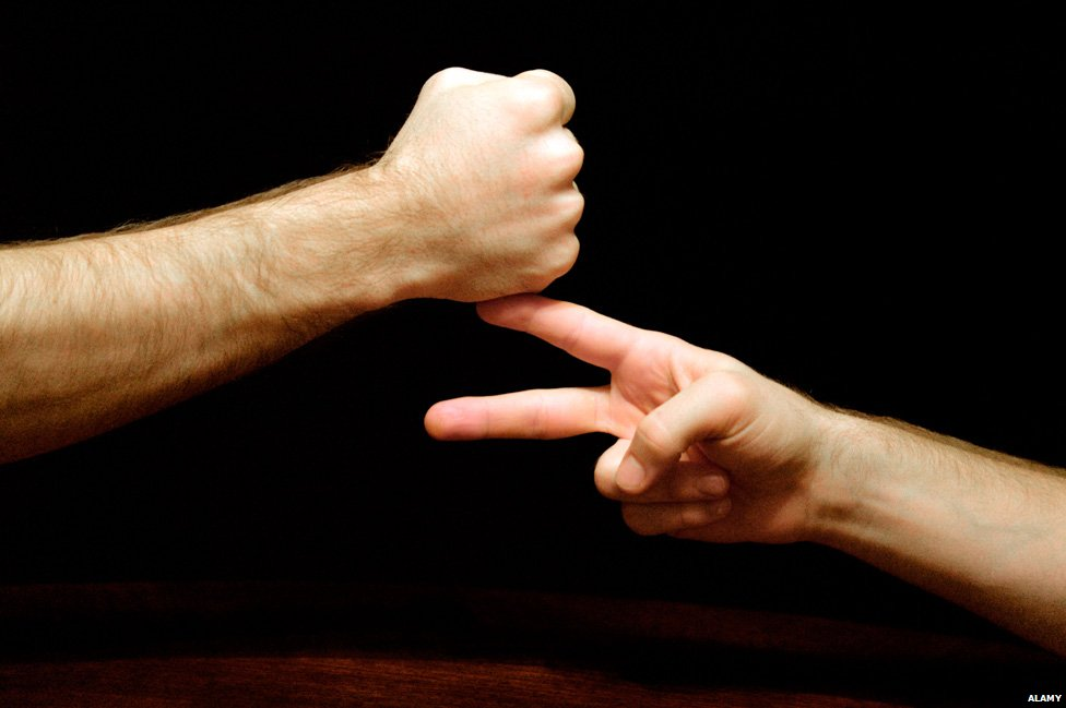 """Two people playing the game """"rock, scissors, paper, stone"""""""