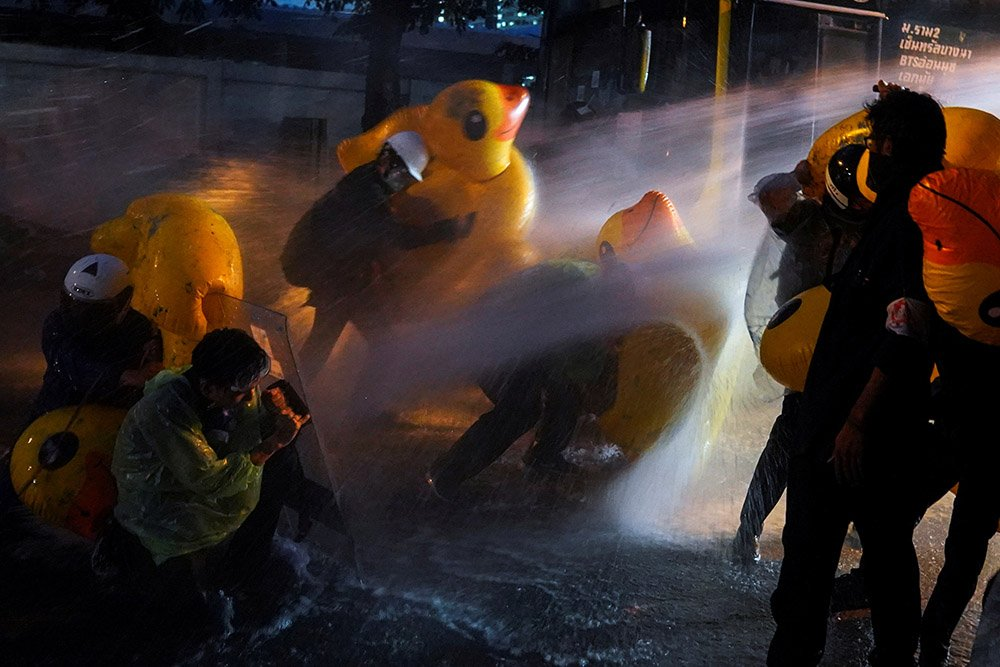 Demonstrators use inflatable rubber ducks as shields