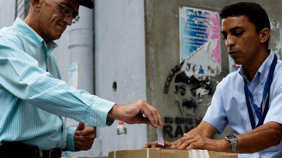 Un señor deposita su voto