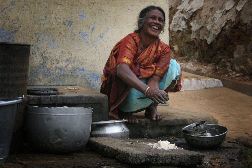 Una mujer lavando platos en India.