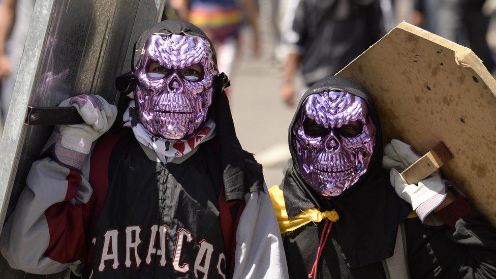 Dos manifestantes con máscaras