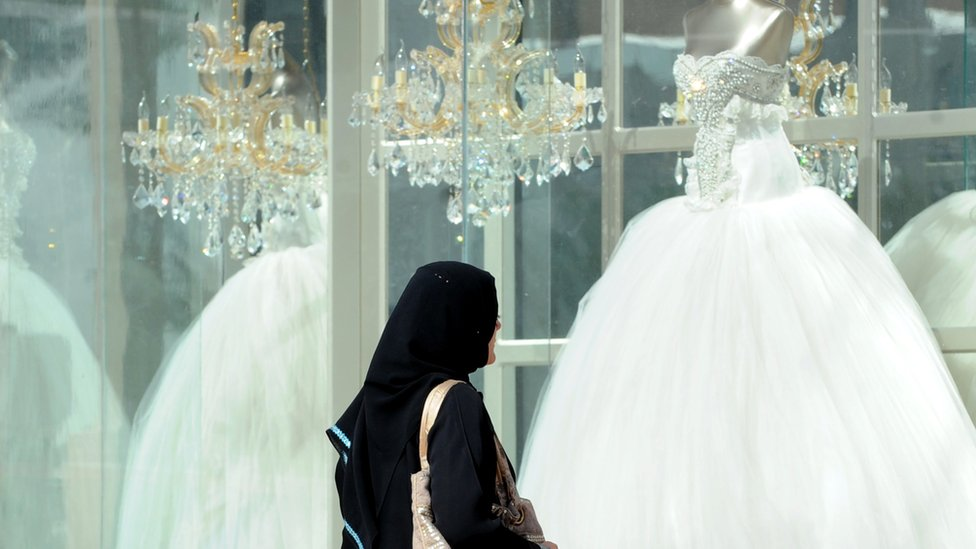 Saudi woman looking at wedding dress