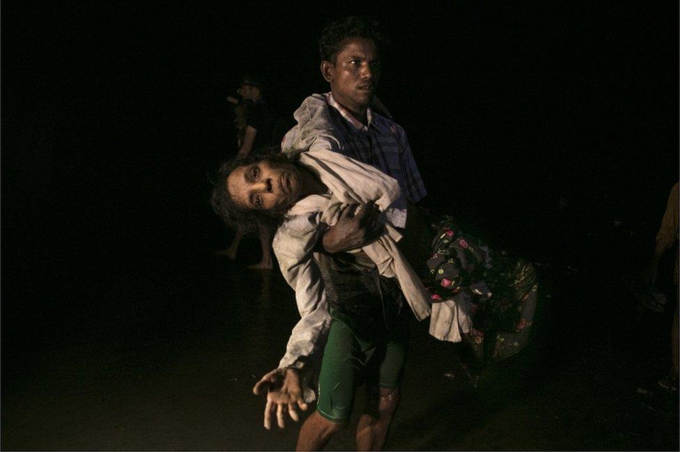 Nobi Hossain carga a Sona Banu hacia la orilla del río Naf. Como ellos, medio millón de rohingyas ha huído a causa de la violencia militar del ejército de Myanmar.