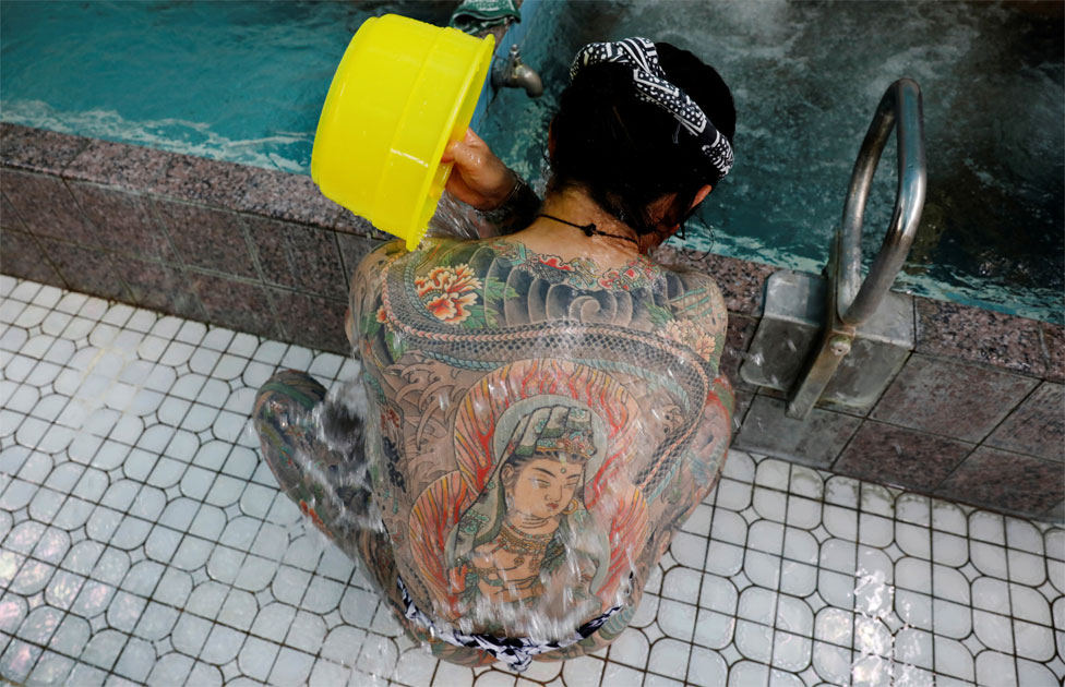 A man with body tattoos pours water over his back