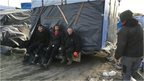 Migrants moving makeshift shacks away from the motorway