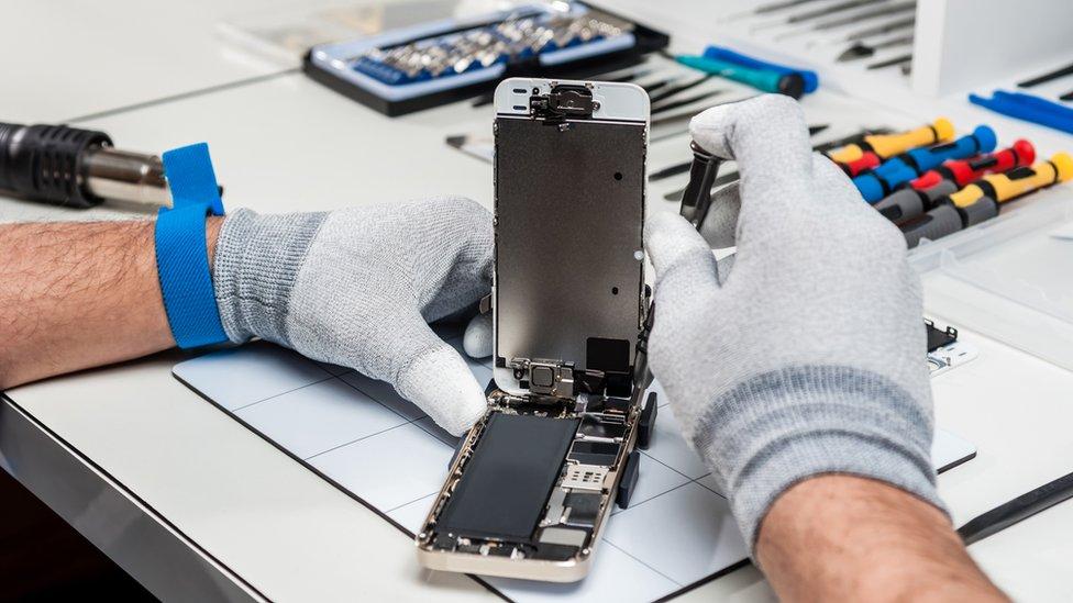 Dos manos reparando un celular en un taller.