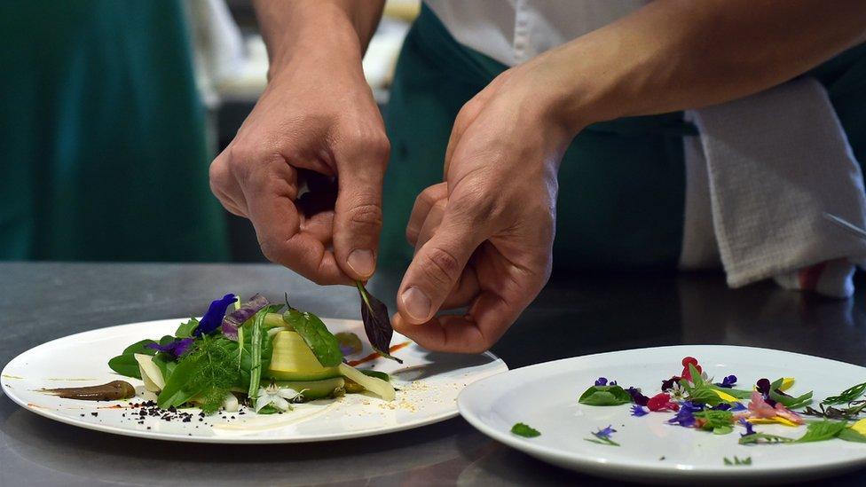 Un chef prepara un plato.