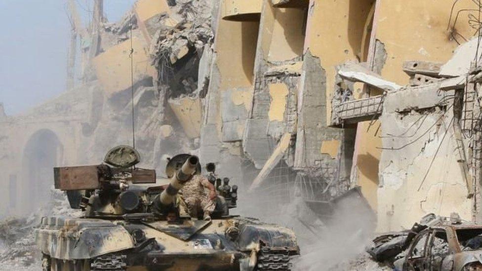 مركبة عسكرية بجوار منزل دمرته الحرب