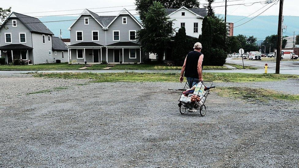 Un hombre empuja un carrito de la compra