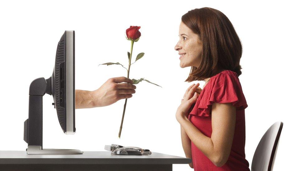 mujer recibiendo una rosa que sale de su computadora