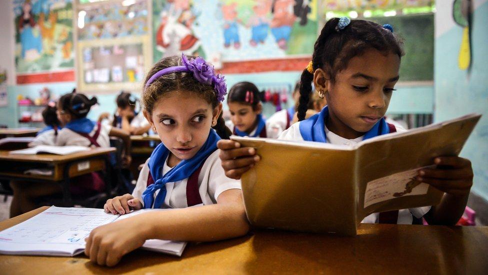 Cuban schoolgirls read during class in Havana