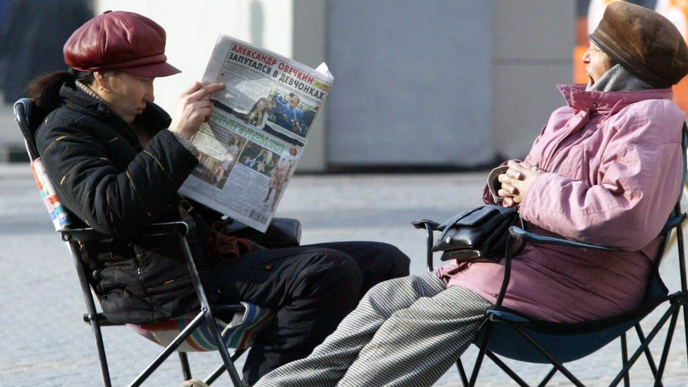 A woman reads a newspaper in Kazakhstan while another looks on.