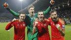 Jubilant players (l-r) Aaron Ramsey, goalkeeper Wayne Hennesey, Gareth Bale and Joe Ledley celebrate on the pitch.