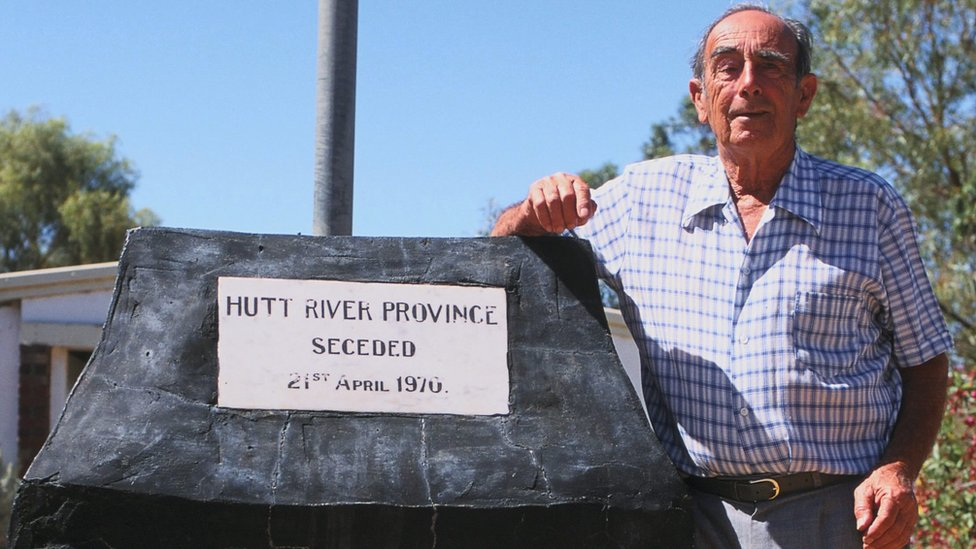 Leonard Casley frente a una placa que conmemora el día en el que declaró su estado independiente el 21 de abril de 1970.