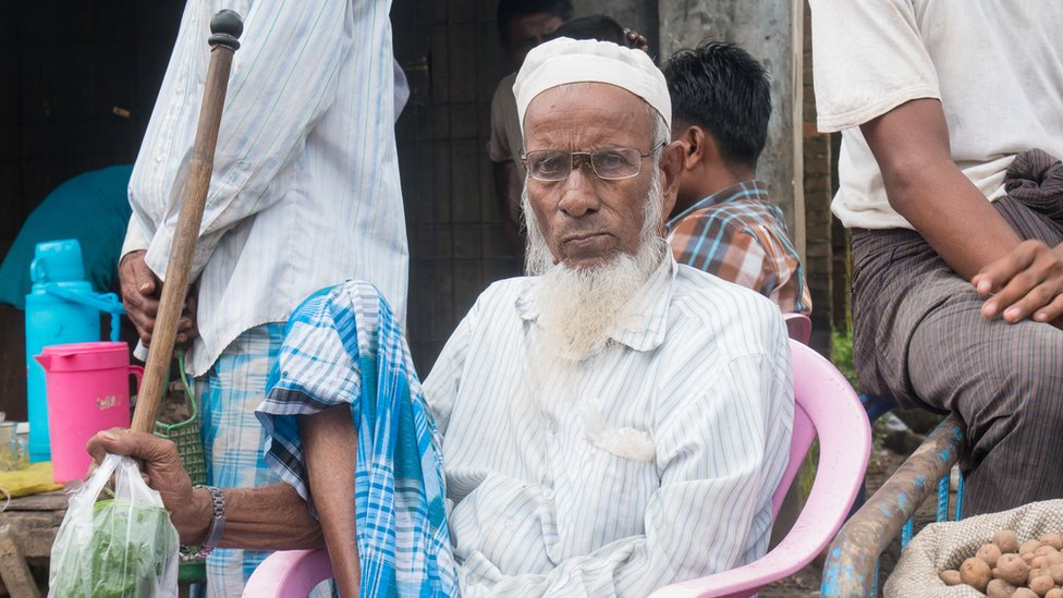 An older Muslim man with a white beard and glasses under his cap sits at the market in Maungdaw, holding a walking cane by his side