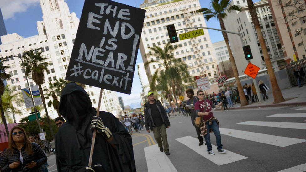 Un manifestante sostiene un cartel con la leyenda