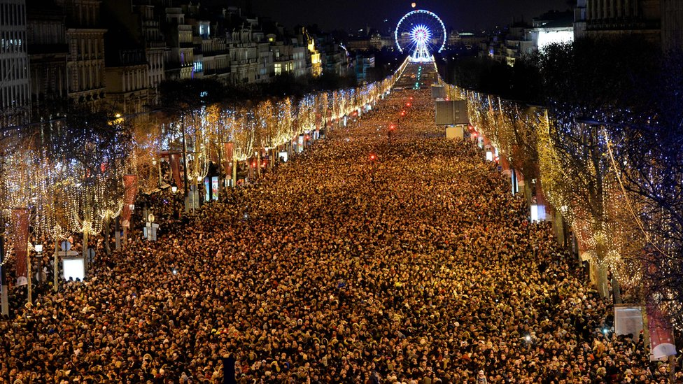 Thousands of people stand on the long avenue in central Paris as far as the ye can see, with a distant Ferris wheel in the background