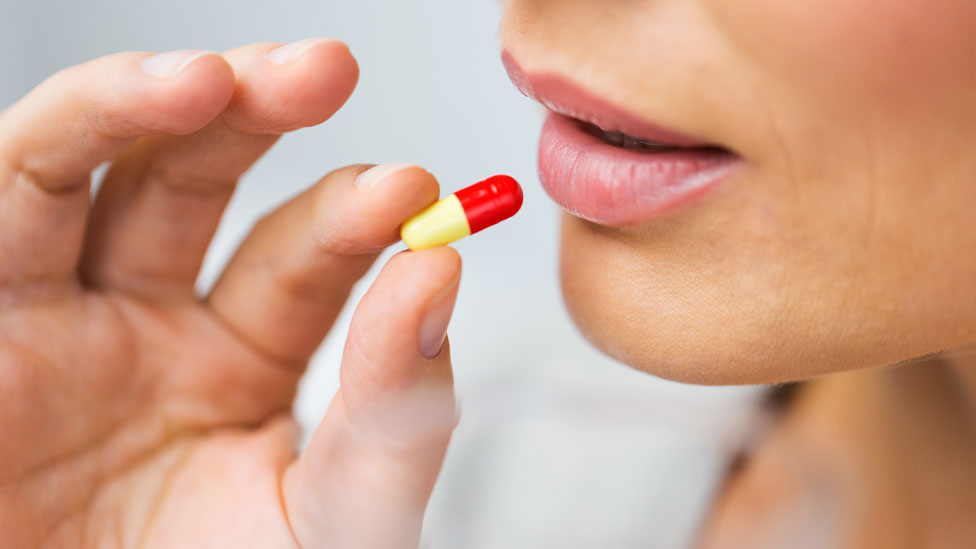 Mujer tomando una píldora