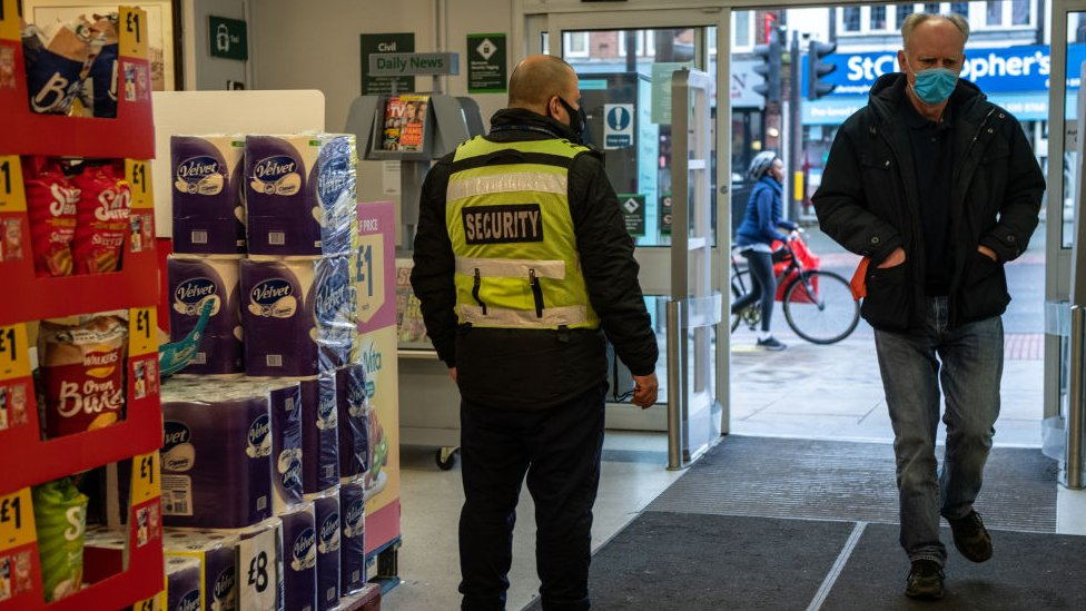 A man wearing a mask walks past a security guard in Morrisons