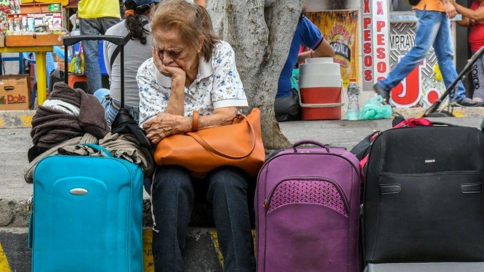 Una mujer sentada junto a varias maletas