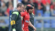 Leigh Halfpenny is helped off after taking a blow playing for Wales against Italy in Rome