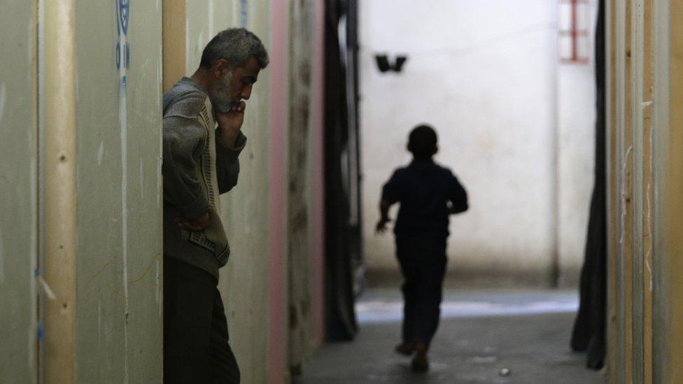 طفل ورجل في ملجأ تابع للحكومة السورية في الغوطة