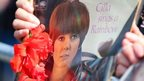 A fan holds a Cilla album on the funeral route