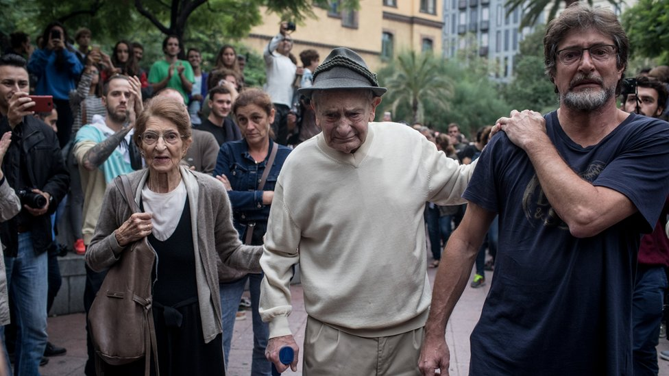 A ninety-year old man is cheered and clapped by the crowd as he leaves after casting his referendum vote at the Escola Industrial of Barcelona school polling station on October 1, 2017 in Barcelona, Spain.