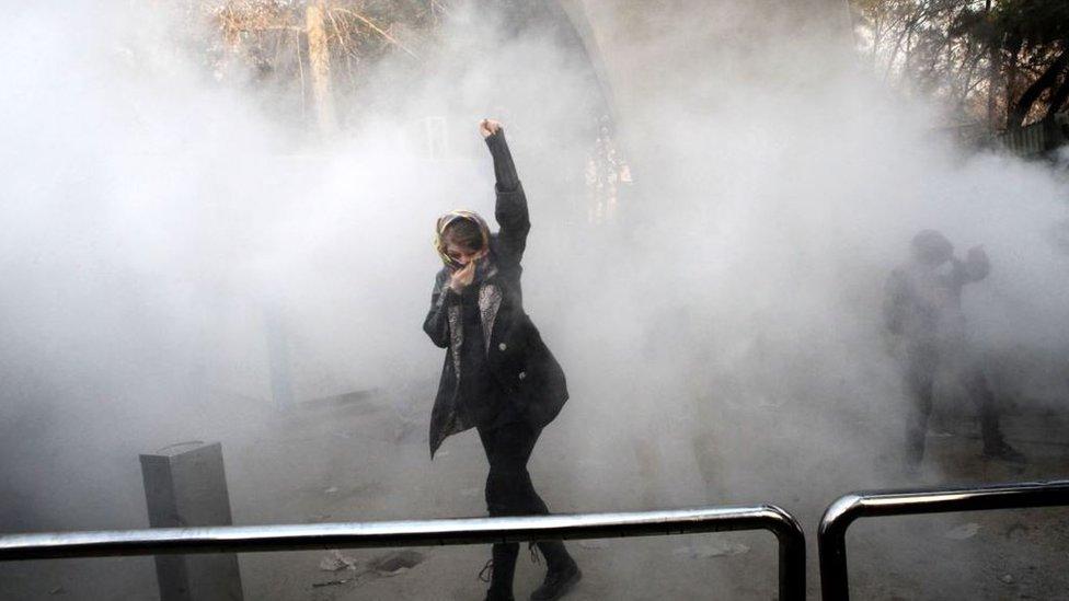 Una joven en medio del gas lacrimógeno