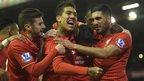Liverpool players celebrate their winner against Swansea