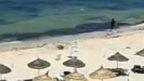 Still from footage showing Tunisia gunman running along beach