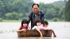 A man pushes a tub carrying children in floodwaters