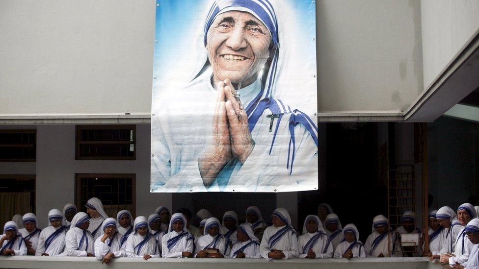 Monjas de las Misioneras de la Caridad bajo una foto de la Madre Teresa durante el décimo aniversario de su muerte en Calcuta, 2007