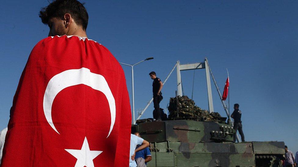 Un joven con una bandera turca pasa frente a uno de los tanques empleados en el fallido intento de golpe de Estado de julio de 2016