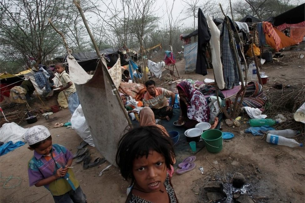 A family, who says they belong to the Burmese Rohingya Community from Myanmar, eats their breakfast at a makeshift shelter in a camp in New Delhi, India, May 14, 2012.