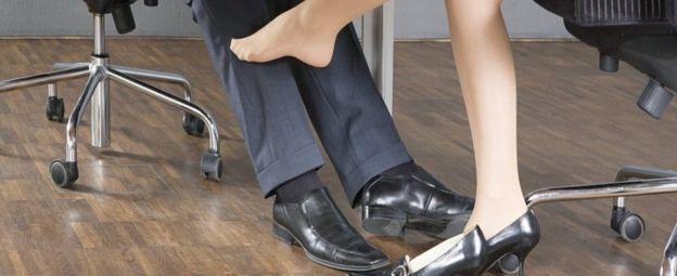 امرأة تلامس بقدمها ساق رجل
