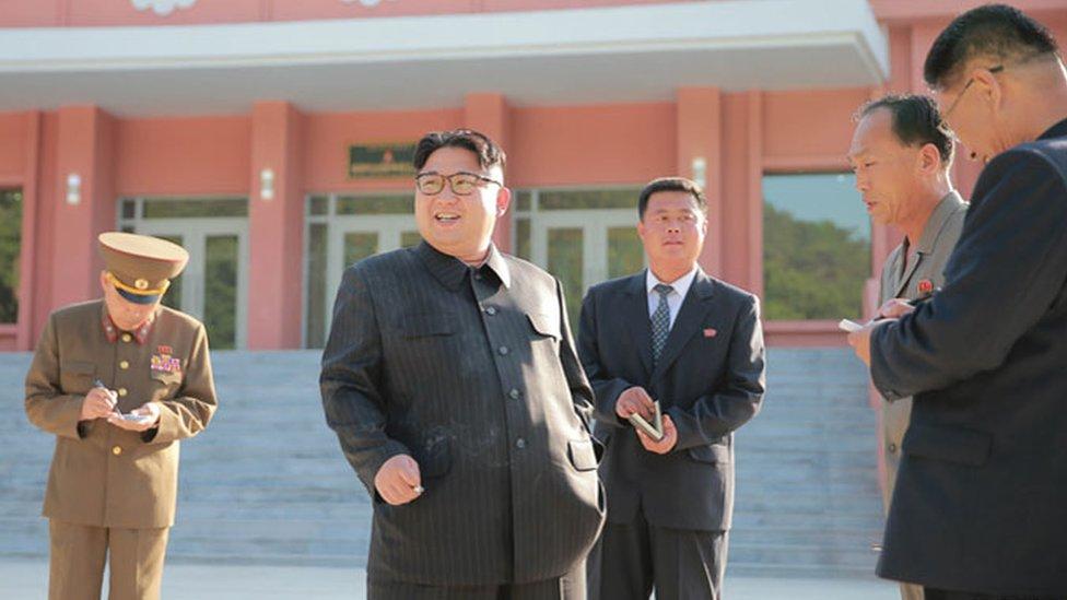 Kim Jong-un smoking a cigarette while officials take notes